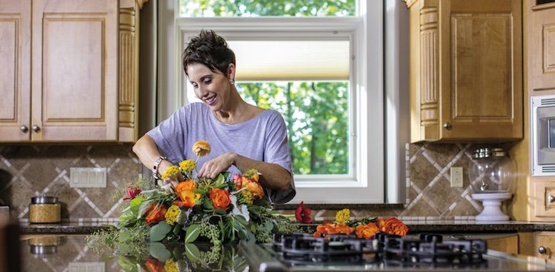 Woman with fresh flowers in her kitchen
